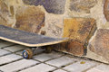 Old skateboard from a stone wall Royalty Free Stock Photo