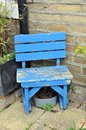 Old small blue wooden chair in a garden outside a house front Royalty Free Stock Photo
