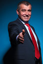 Old smiling business man welcomes you with a handshake on blue background Stock Image