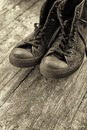 Old sneakers black on wooden floor monochromatic image Royalty Free Stock Image