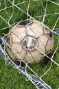 Old soccer ball in the goal net on green grass Stock Photos