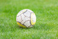 Old soccer ball on green grass Royalty Free Stock Photo