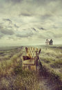 Old sofa chair in tall grass on path Royalty Free Stock Photo