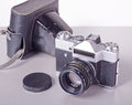 Old soviet film slr camera with a leather case zenit e prime lens and on grey background Stock Images
