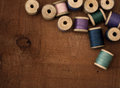 Old spools of thread on a wooden background Stock Photos