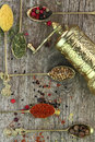 Old spoons with spices and pepper grinder on wooden background Stock Photo