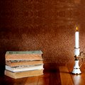 Old stack of books with candlestick and burning candle on the wooden table Stock Photos