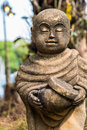 Old statue of a little monk standing and holding monk s alms bowl closed eyes Royalty Free Stock Photography