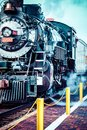 Old steam locomotive against blue cloudy sky, vintage train Royalty Free Stock Photo