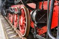 Old steam train wheels approaching, close-up. Black and red wheels. Rails and sleepers. Royalty Free Stock Photo