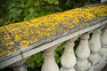 Old stone balustrade covered with yellow moss Royalty Free Stock Photo