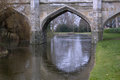 Old stone bridge arches with moat in England Royalty Free Stock Photo