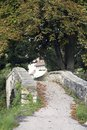 Old stone bridge peaceful picture showing a small alley over a in front of big trees and a small village at autumn time Royalty Free Stock Images
