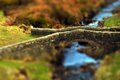 Old stone bridge tilt and shift photograph of an crossing a stream Royalty Free Stock Photo