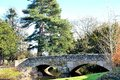 old stone bridge and tree reflections in a river Royalty Free Stock Photo