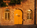 Old stone building with yellow door and windows two rails in late afternoon sun Royalty Free Stock Photo
