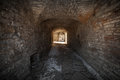 Old stone fortress dark stone tunnel perspective with glowing end Stock Photos