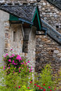 Old stone house building with pink rose plant in france Stock Image
