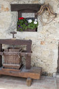 Old stone house exterior with wooden window yoke and traditional wine press Stock Photo