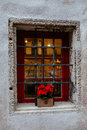 Old stone house`s window decorated with colorful petunia flowers in medieval old town of Tallinn, Estonia Royalty Free Stock Photo