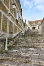 Old stone stairway leading to a church up above with worn steps and vintage lamp post on hill with cross in symbolic Royalty Free Stock Photography