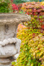 Old stone vase in autumn park with blured vine foliage background Royalty Free Stock Photography