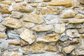 Old stone wall made from river rocks hard uneven building background Stock Images