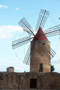 Old stone windmill with six vanes historical for generating power and energy behind a wall Stock Photos