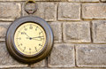 Old street clock on a stone wall Stock Photo