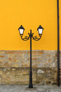 Old street lamp with orange wall painted Royalty Free Stock Photography