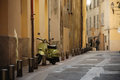 Old street of nice empty with special columns along and green motorcycle parked fawn coloured walls houses Royalty Free Stock Photography