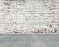 Old stripped bricks wall with green wooden floor