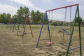 Old style children playground located near the parking this is a little equipped with a basic metal swings and metal see saws most Royalty Free Stock Image