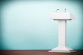 Old style photo white podium tribune rostrum stand with microph microphones on the floor Royalty Free Stock Photo