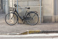 Old styled Bicycle with basket parking near street. Chained black bike in the corner Royalty Free Stock Photo