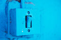 The old switch in the web on the blue brick wall.