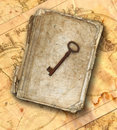 Old tattered book with rusty key on the old maps Royalty Free Stock Photo