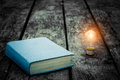 Old tattered book on a wooden table. Reading by candlelight. Vintage composition. Ancient library. Antique literature. Royalty Free Stock Photo