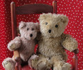 Old teddy bears in a red chair Stock Image