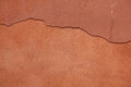 Old terracotta painted stucco wall with cracked plaster. Background texture Royalty Free Stock Photo