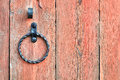 Old textured light red wooden door with aged metal door handle in the form of ring. Royalty Free Stock Photo