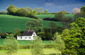 Old thatched cottage, rolling farmland, dappled sunlight Royalty Free Stock Photo