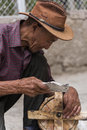 Old Tibetan man cleaning ancient wooden prayer wheel