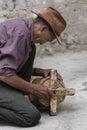 Old Tibetan man repairing ancient wooden prayer wheel