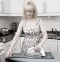 Old time ironing desaturated vintage style photo of woman in the kitchen Stock Photos
