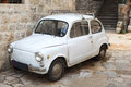 Old-timer white small italian car parked in an all Royalty Free Stock Photo