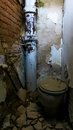 Old toilet an dilapidated with waste pipe and masonry Stock Images