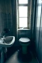 Old toilet an with window in background Royalty Free Stock Photo