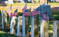 Old tomb stones veterans from early wars are still remembered as american flags are placed by them on memorial day Royalty Free Stock Photo