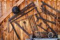 Old tools in wood shed hanging on the wall grunge background Stock Photo